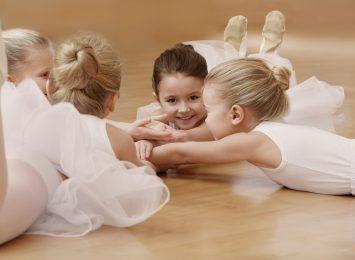 Group of beautiful little ballerinas resting on the floor